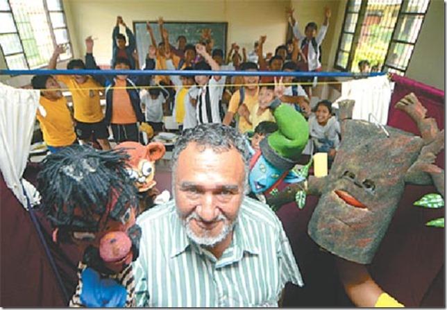 Zenón Quiroz con sus títeres. Al fondo los niños de la escuela Max Fernández, a quienes visitó miércoles