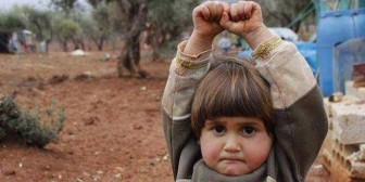"""Conmoción en redes por foto de niña siria que se """"rinde"""" ante una cámara"""