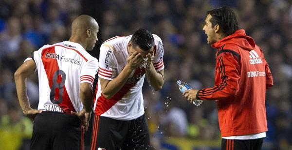 El defensor Ramiro Funes Mori (centro) es asistido por dos de sus compañeros tras recibir el gas pimienta en la manga que conecta a los vestuarios y el campo de juego