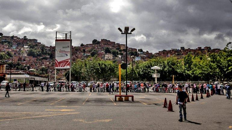 Decenas de venezolanos esperan en fila para ingresar a un supermercado en Caracas