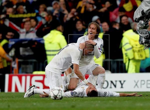 Los jugadores del Real Madrid Cristiano Ronaldo (en el suelo), Luka Modric (d) y Pepe, celebran la clasificación de su equipo tras vencer al Wolfsburgo por 3-0 en el partido de vuelta de cuartos de final de la Liga de Campones que se jugó en el estadio Santiago Bernabéu, en Madrid. EFE