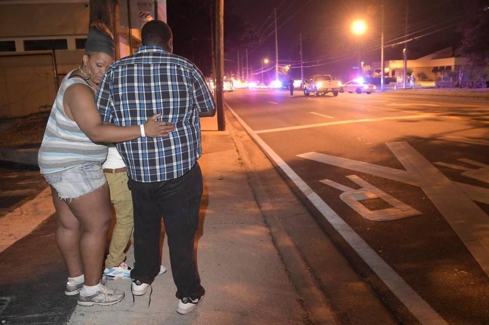 Transeúntes esperan en la calle tras el tiroteo múltiple en el club nocturno Pulse en Orlando, Florida.