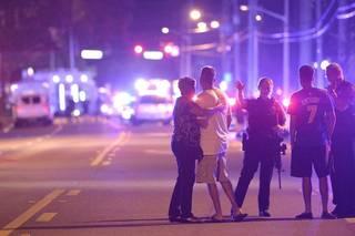 Agentes de policía de Orlando hablan con familiares en un tiroteo múltiple en un club nocturno en Orlando, Florida.