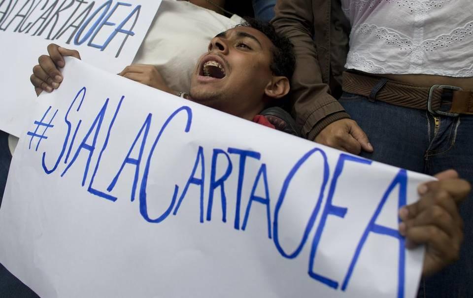 Un simpatizante de la oposición venezolana se manifiesta a favor de la aplicación de la carta democrática frente a las oficinas de la OEA en Caracas el 23 de junio del 2016. Ariana Cubillos AP