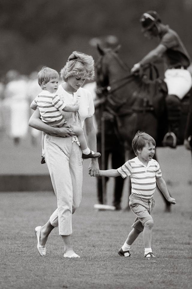 Diana con el príncipe Harry en brazos (y Guillermo de la mano) en un partido de polo.