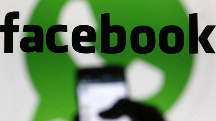 Imagen ilustrativa de un hombre usando WhatsApp en su teléfono inteligente con el logo de Facebook en el fondo.