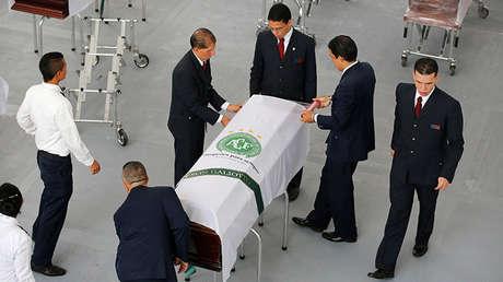Personal funerario prepara un ataúd con los restos de una víctima del vuelo siniestrado del club Chapecoense.