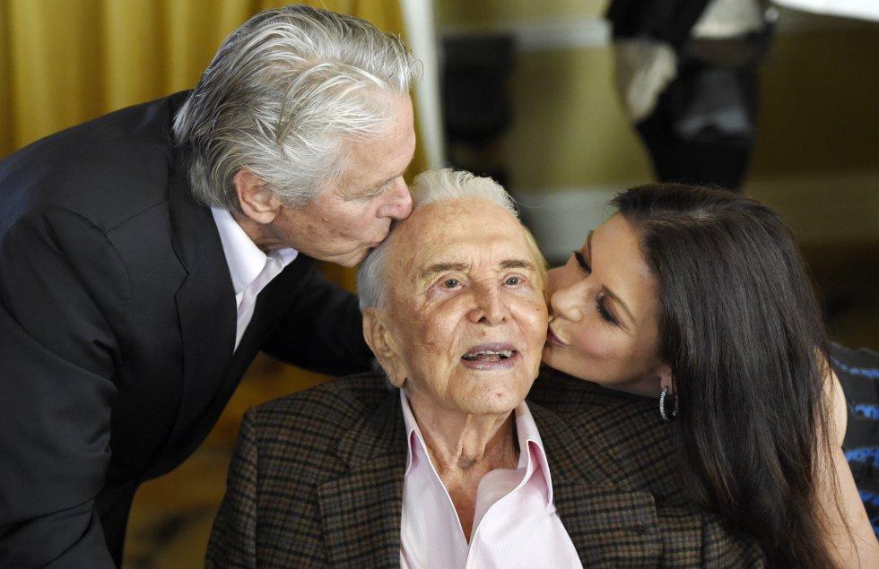 El actor Kirk Douglas, besado por su hijo Michael Dougas y por la esposa de este, Catherine Zeta-Jones, en la fiesta por sus cien años en el hotel Beverly Hills, de California, ayer viernes.
