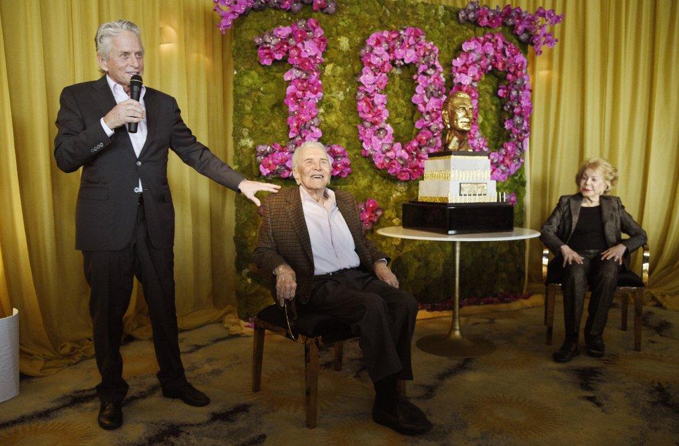 Kirk Douglas, sentado, escucha a su hijo Michael, también actor, que se dirige a los invitados en el hotel Beverly Hills. A la derecha de la gran estrella del cine su esposa, Anne.
