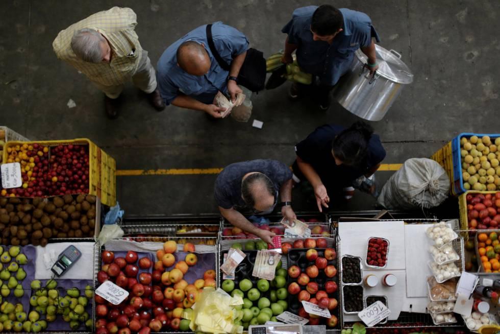 Los clientes cuentan bolívares en un mercado de Caracas.