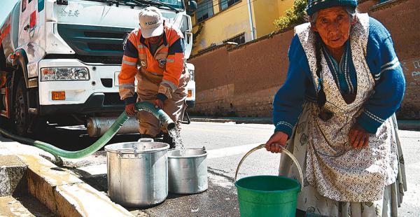 Una persona de la tercera edad intenta cargar agua para llevar a su casa, en una zona alta de La Paz