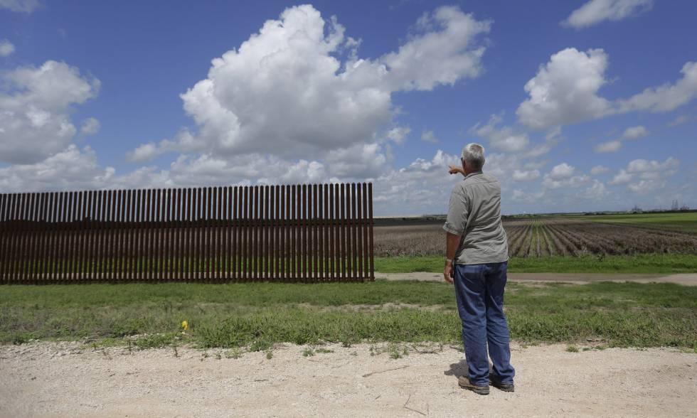 Un hombre señala un tramo de la valla fronteriza en Brownsville (Texas) en una imagen de 2005