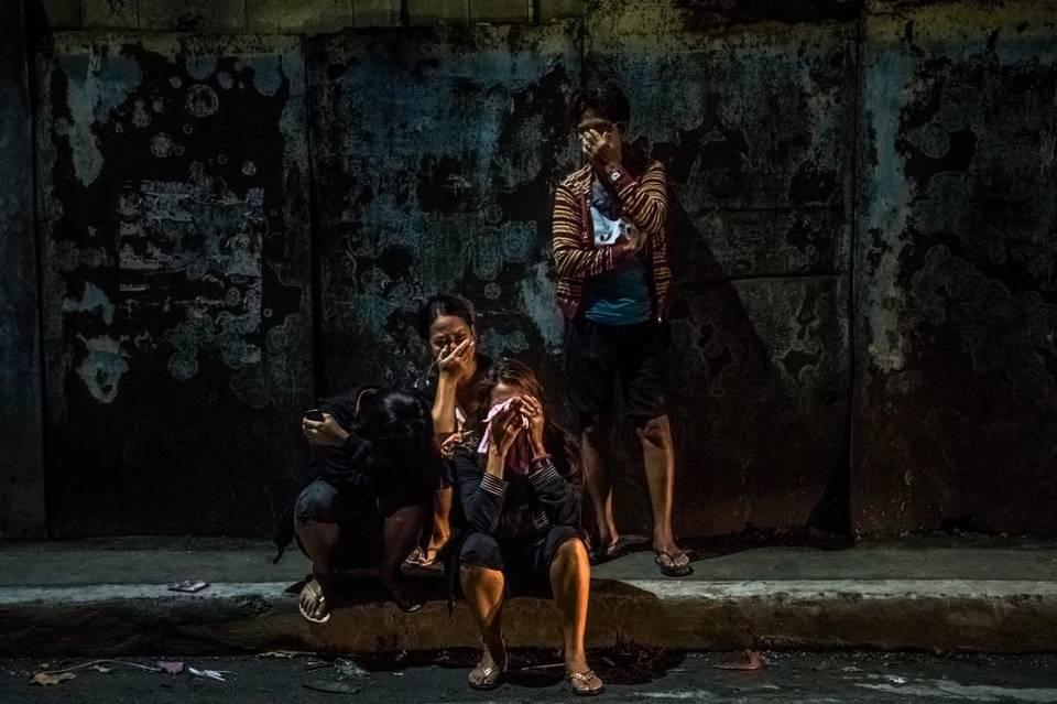 Familiares de las víctimas lloran en la calle donde yacen los cuerpos de Frederick Mafe y Arjay Lumbago en Manila, Filipinas, el 3 de octubre.