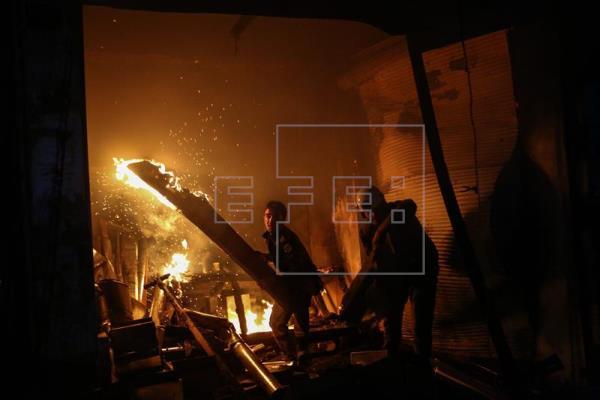 Voluntarios de la Defensa Civil siria, conocidos como Cascos Blancos, apagan un incendio tras un bombardeo en Douma, Siria. EFE/Archivo
