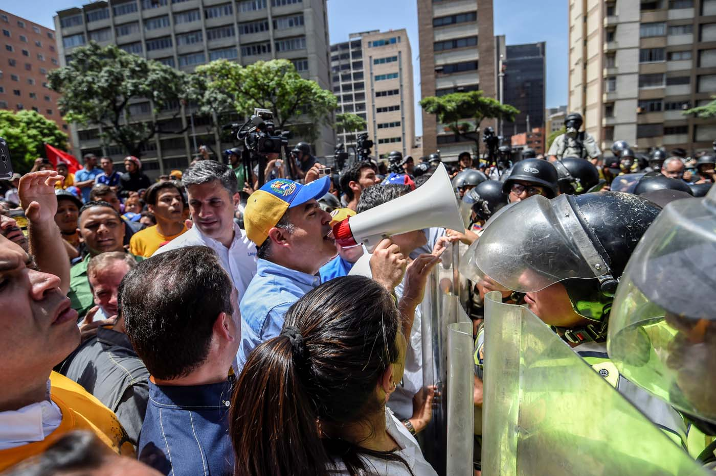 The President of the National Assembly Julio Borges using a megaphone addresses riot police agents during a protest against Nicolas Maduro