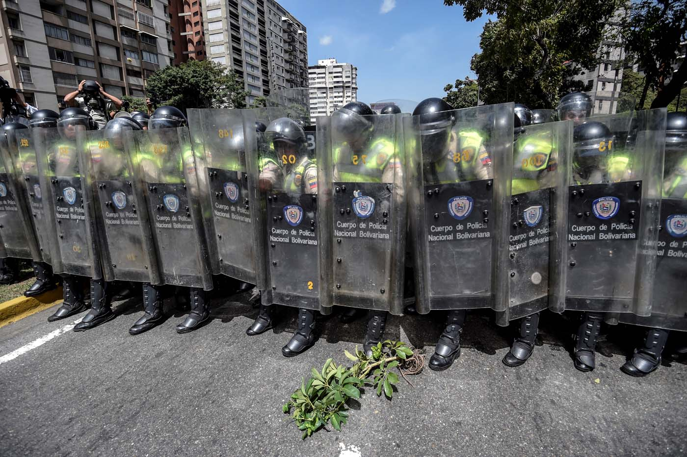 Riot police officers block an avenue during a protest against Nicolas Maduro