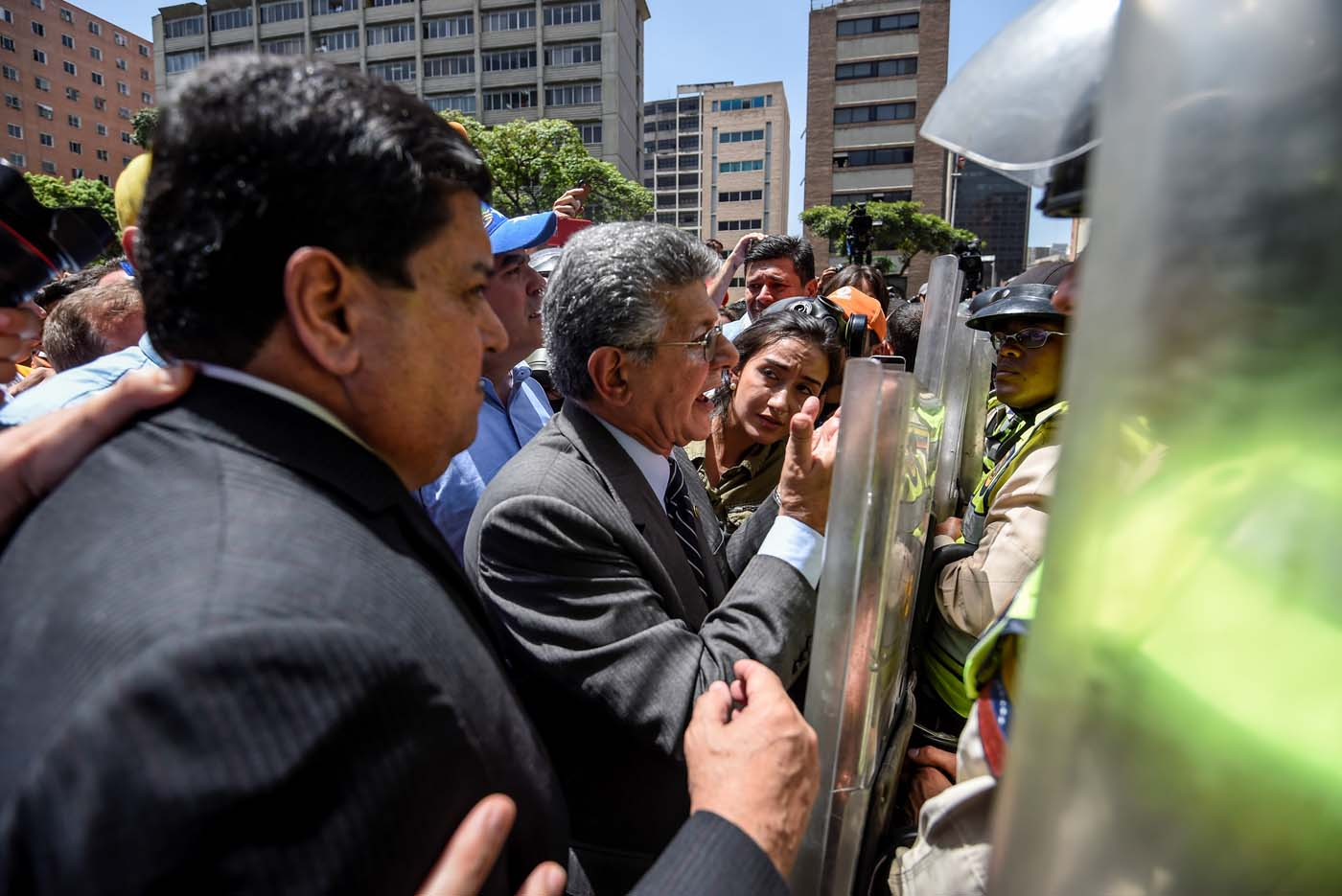 Former President of the Venezuelan National Assembly Henry Ramos Allup(C) speaks with riot police officers during a protest against Nicolas Maduro