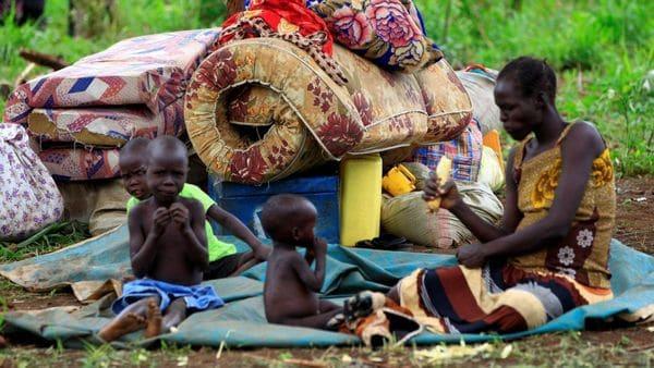 Una mujer sudanesa obligada a desplazarse con su familia hacia Uganda por los enfrentamientos en su país (Reuters)