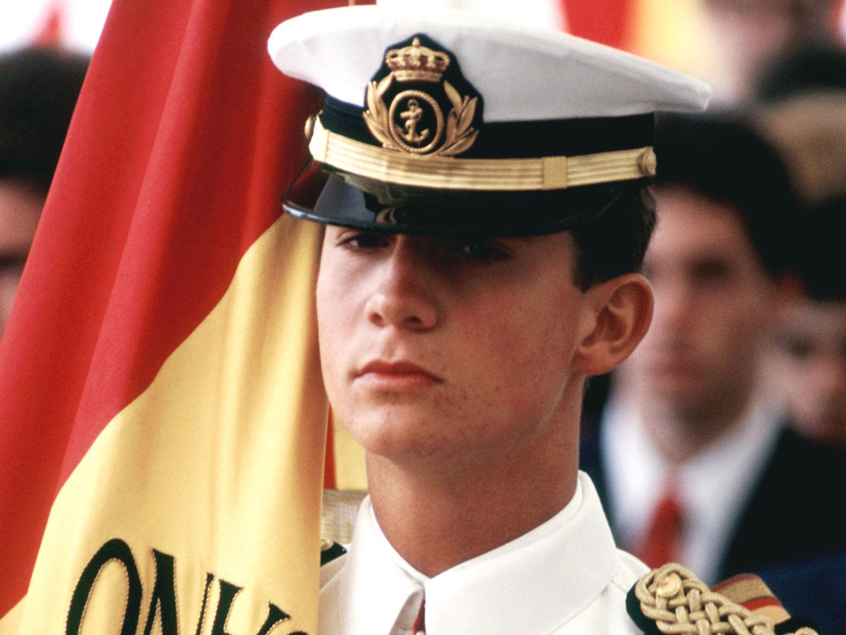 El entonces príncipe con uniforme de cadete y la bandera del buque Juan Sebastián Elcano durante un acto oficial.