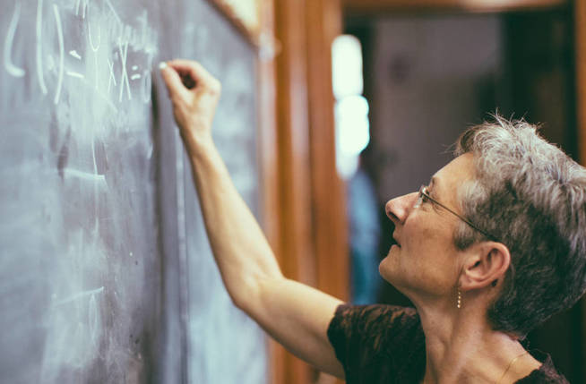 Concentrated senior female mathemathics professor writing a formula to the chalkboard.. Personal Perspective, Selective focus, small DOF. Natural interior light.