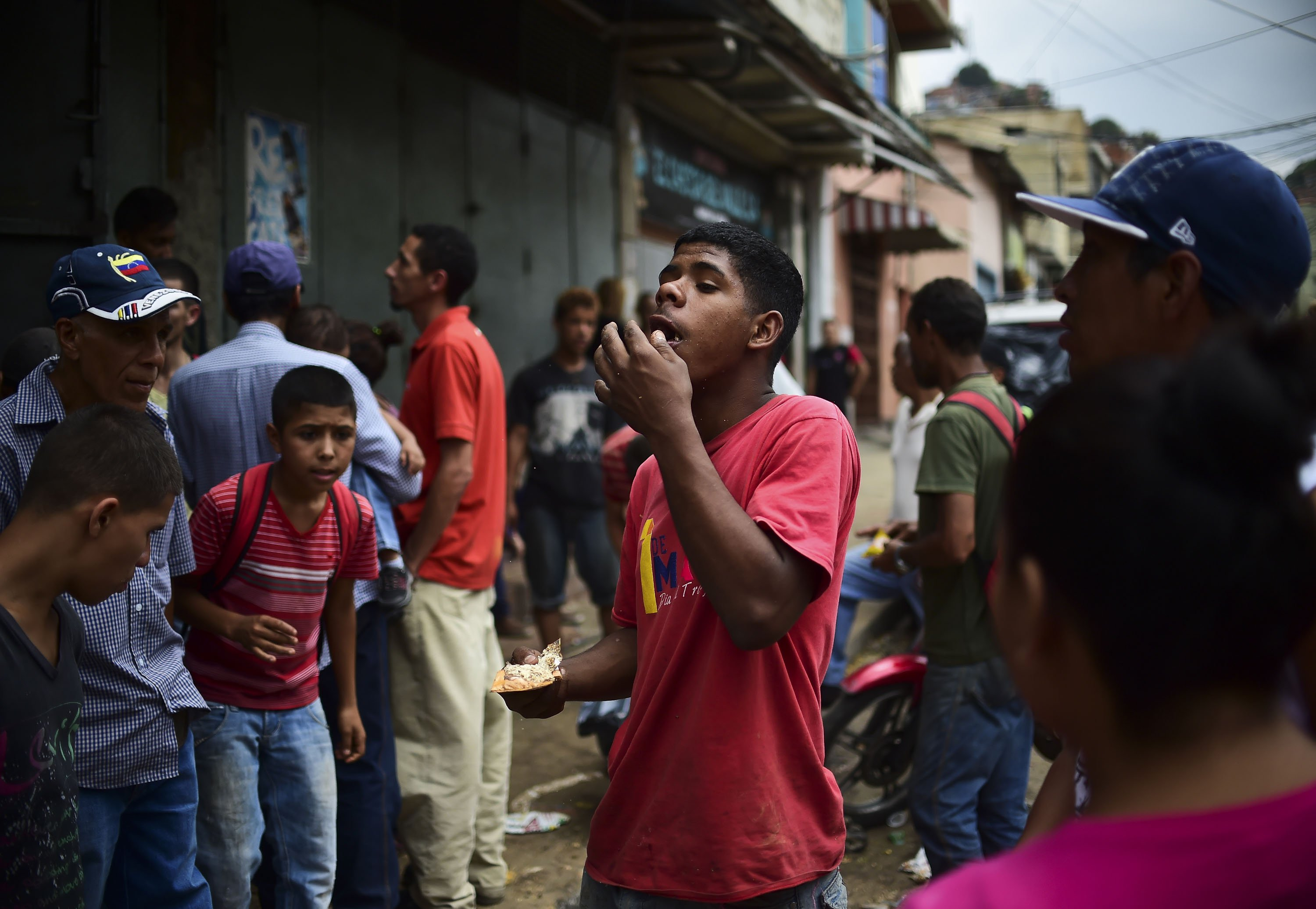 A man eats food he found outside a looted supermarket at El Valle neighborhood, in Caracas, on April 21, 2017, after demonstrations against the government of Venezuelan President Nicolas Maduro. Venezuela was rocked overnight by fresh violence in anti-government protests that have now claimed nine lives in three weeks, as an official reported Friday the fatal shooting of another man. / AFP PHOTO / RONALDO SCHEMIDT