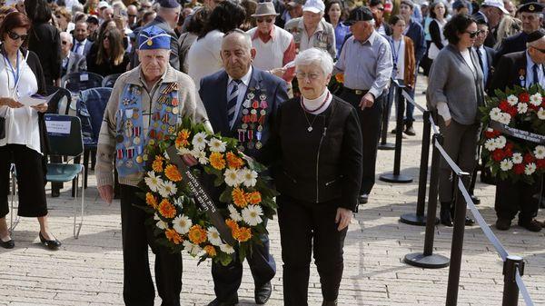 Veteranos de la Segunda Guerra Mundial dejan una corona de flores en la ceremonia de inicio del Día del Recuerdo del Holocausto(AFP)
