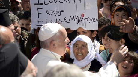 El Papa Francisco saluda a migrantes y refugiados en el campo de refugiados de Moria, en la isla griega de Lesbos, 16 de abril de 2016