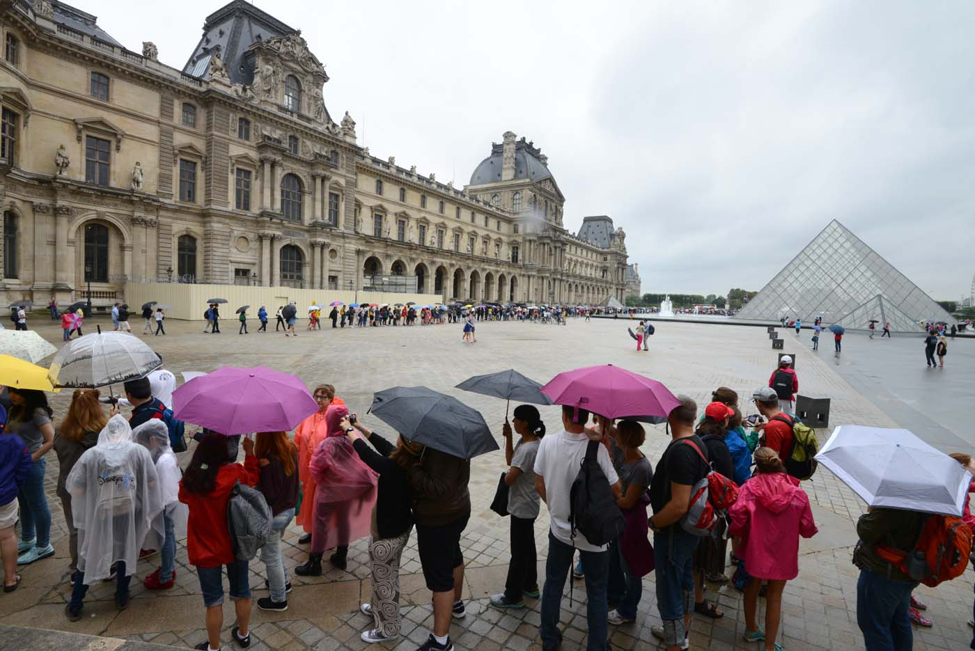 (FILES) This file photo taken on August 08, 2014 shows people queueing under the rain to get in the Louvre Museum in Paris. After a decline in 2016 due to the terror attacks in Paris and Nice, tourism in Paris and Ile de France is in much better shape in the first half of 2017, with 1,5 million tourists and 3,3 million overnight stays more than a year ago. / AFP PHOTO / DOMINIQUE FAGET