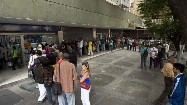 Decenas de personas hacen fila en un banco de Caracas para sacar de dinero. (AFP)
