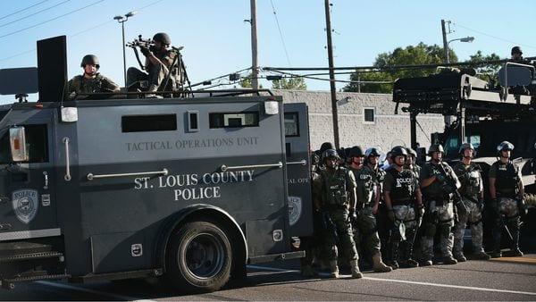 Chalecos, fusiles de asalto y francotirador y un vehículo blindado durante las protestas en Ferguson en 2015 que llevaron al presidente Obama a limitar ese equipo (AFP)