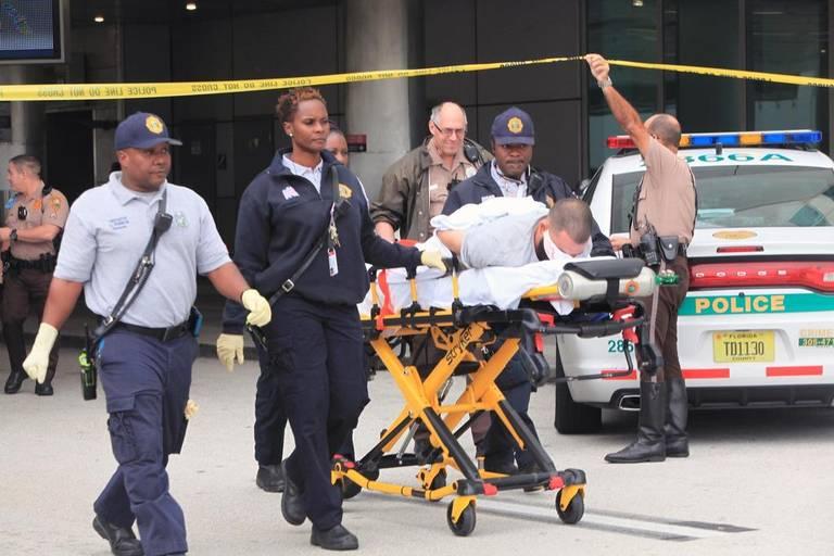 La policía de Miami-Dade vigila a un hombre que yace en el suelo frente al Concourse D en el Aeropuerto Internacional de Miami después de un aparente altercado el miércoles 25 de octubre de 2017.