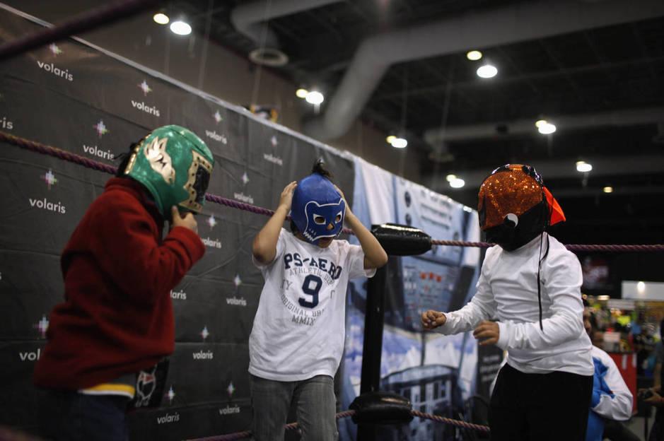 Unos niños se prueban máscaras de lucha libre durante una exposición sobre este deporte en Ciudad de México, en agosto de 2012. (Reuters)