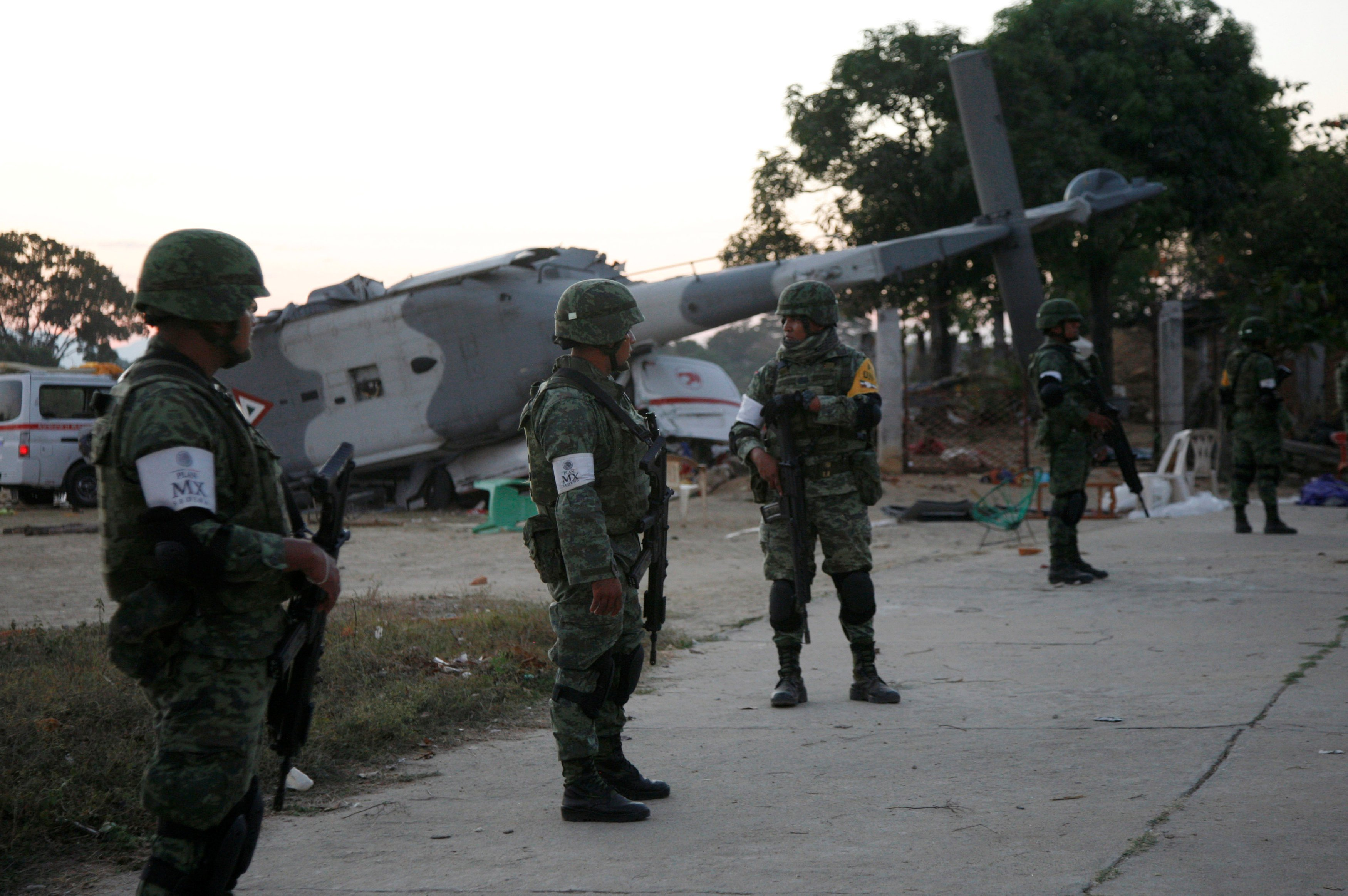 Soldiers stand guard next to a military helicopter, carrying Mexico