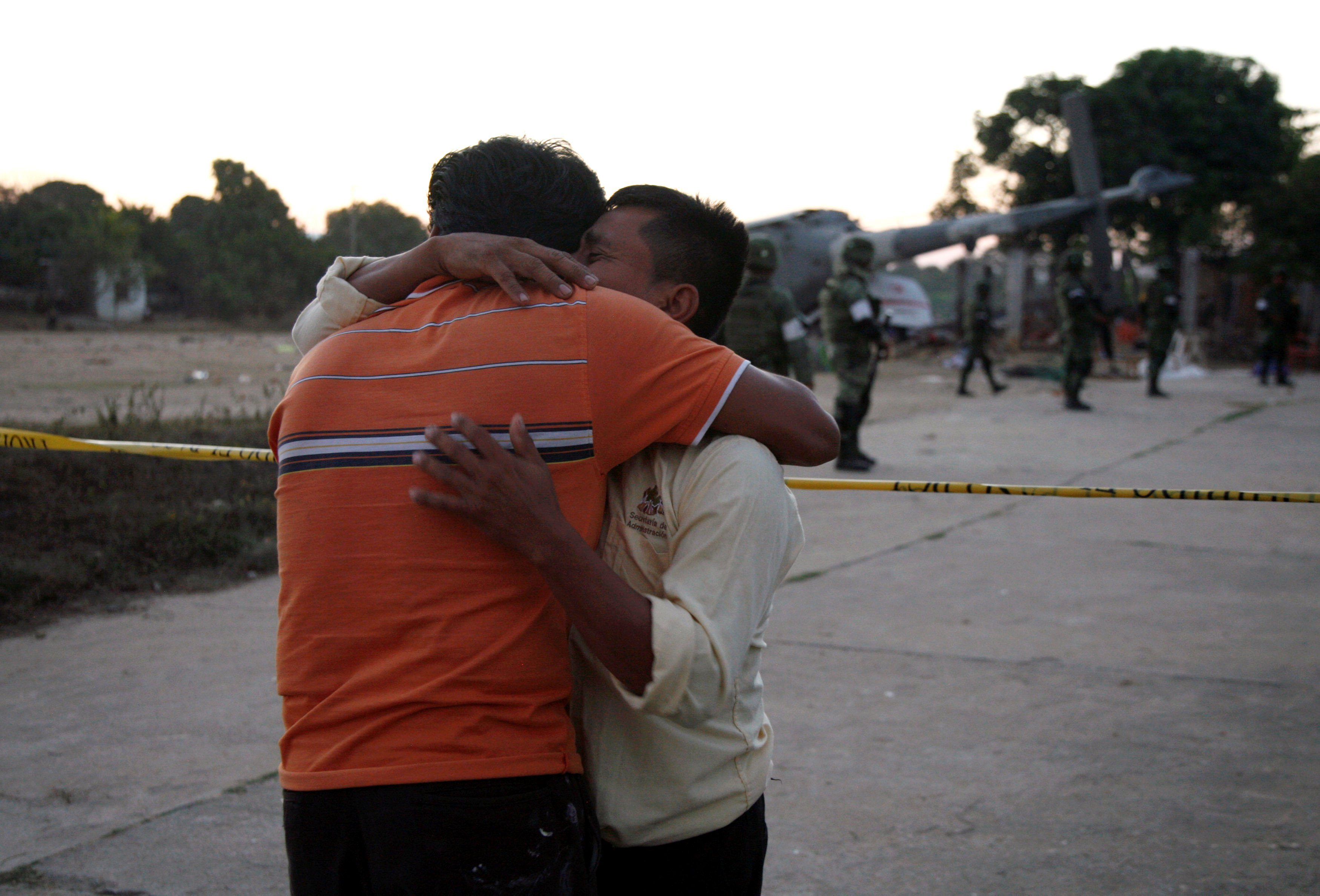 People react as soldiers stand next to a military helicopter, carrying Mexico