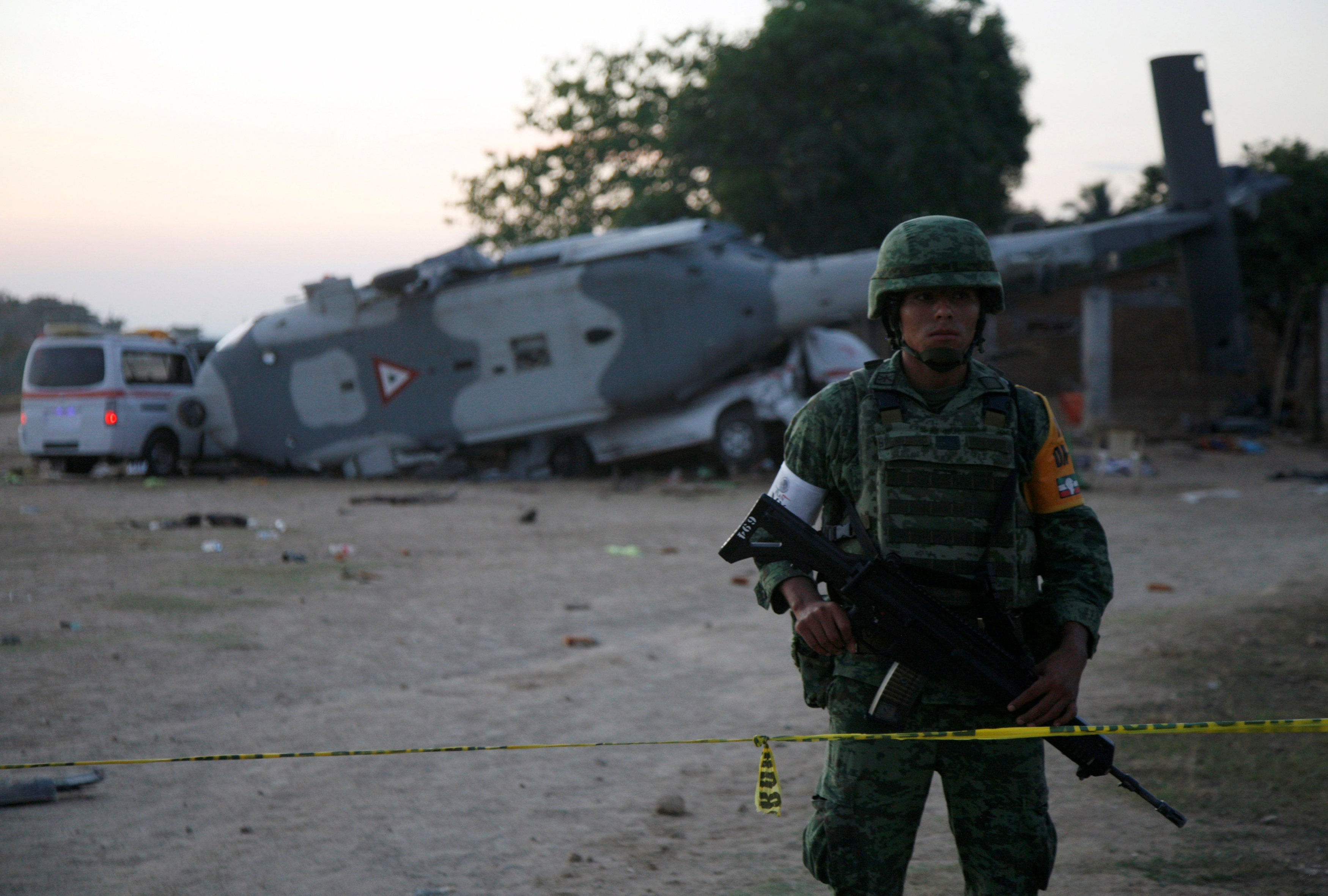A soldier stands guard next to a military helicopter, carrying Mexico