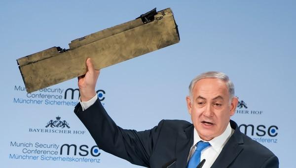 El primer ministro Benjamin Netanyahu muestra un pedazo del drone iraní derribado sobre cielo israelí (AFP)