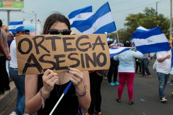 Una mujer sostiene un cartel en protesta por los muertos en la protestas contra el régimen de Ortega. (REUTERS/Oswaldo Rivas)