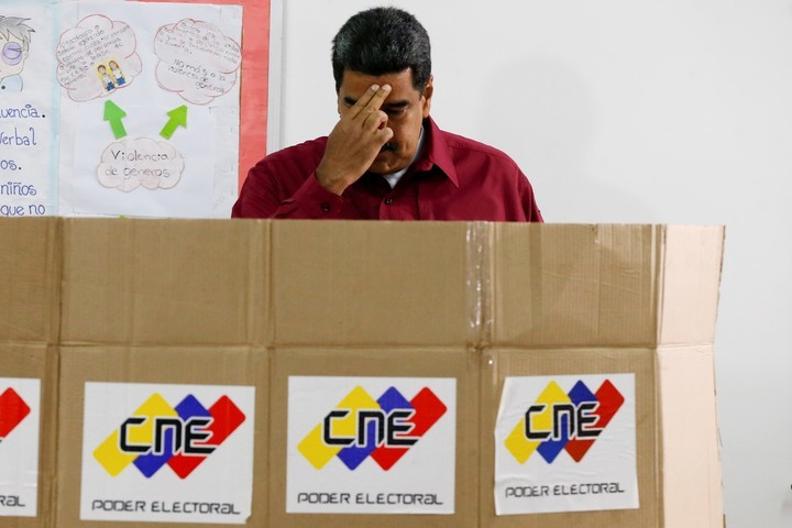 Nicolás Maduro se persigna antes de emitir su voto. AP