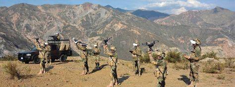Un grupo de militares controla drones en una cima.