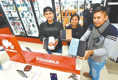 Venta. Jóvenes del local San Miguel, en la Eloy Salmón, muestran las marcas Xiaomi, Samsung y Huawei.