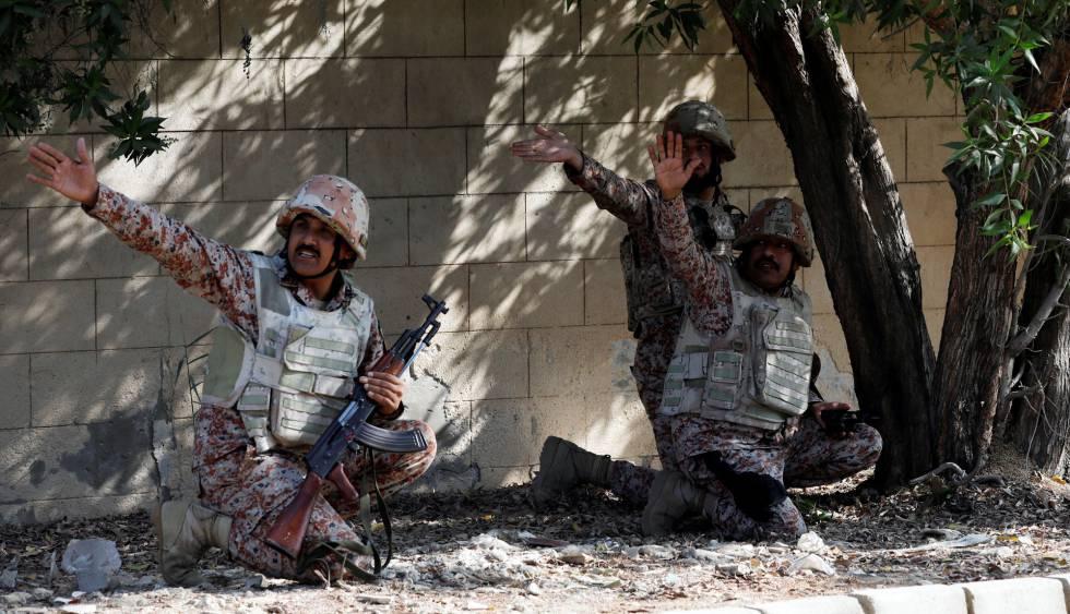 Tres militares paquistaníes se cubren durante el ataque al consulado chino en Karachi (Pakistán).