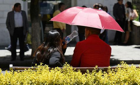 Una pareja en el Prado de La Paz se protege de los rayos solares.
