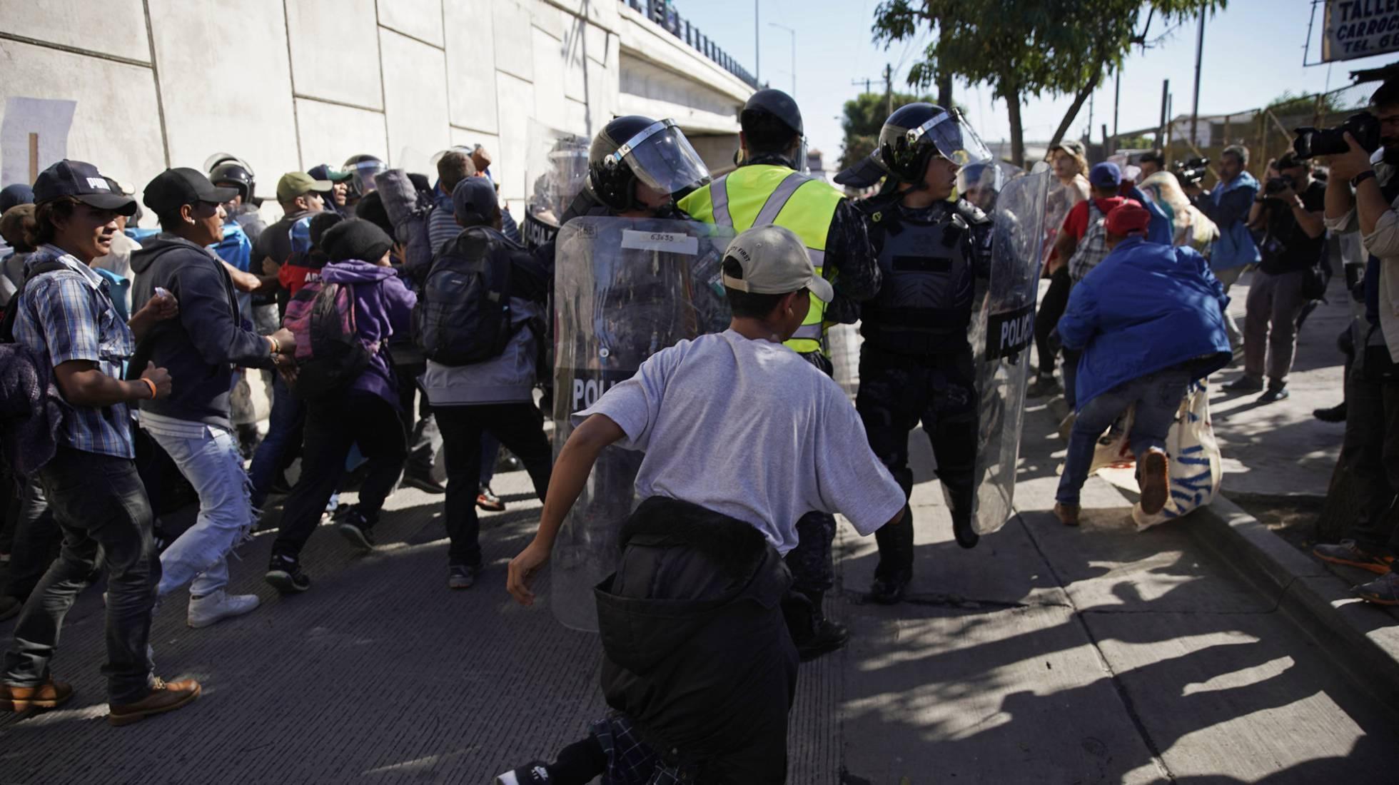 Migrantes rompen el cerco policial en Tijuana, México.