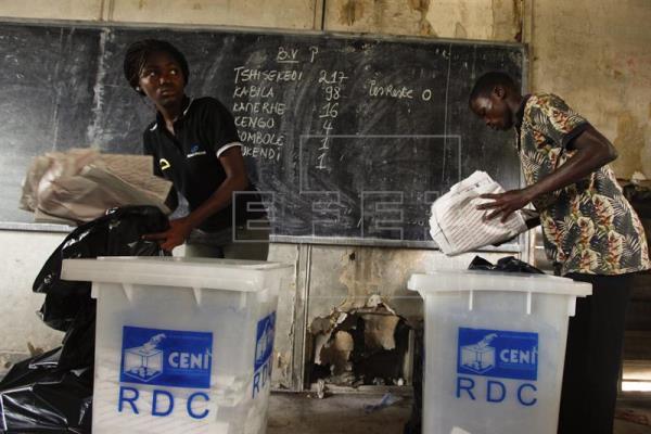 Dos agentes electorales recogen las papeletas de votación en un colegio electoral de Kinshasa, en la República Democrática del Congo. EFE/Archivo