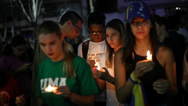 Un grupo de jóvenes sostiene unas velas durante una vigilia en Caracas. (Reuters)