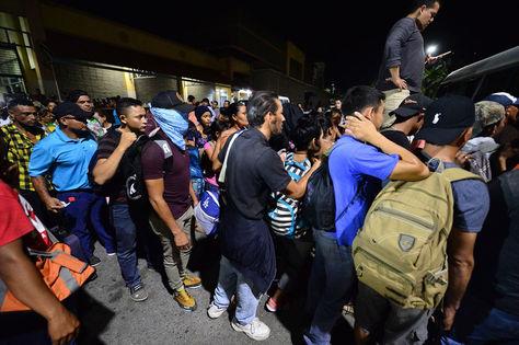 Familias hondureñas hacen fila para abordar un autobús en San Pedro Sula, a 300 km al norte de Tegucigalpa, con rumbo a Guatemala. Foto: AFP