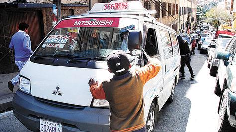 Menor limpia parabrisas de los vehículos en el centro paceño