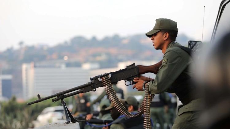 Un miembro de las fuerzas opositoras toma posición. Los pañuelos azules marcan pertenencia al levantamiento (Reuters)