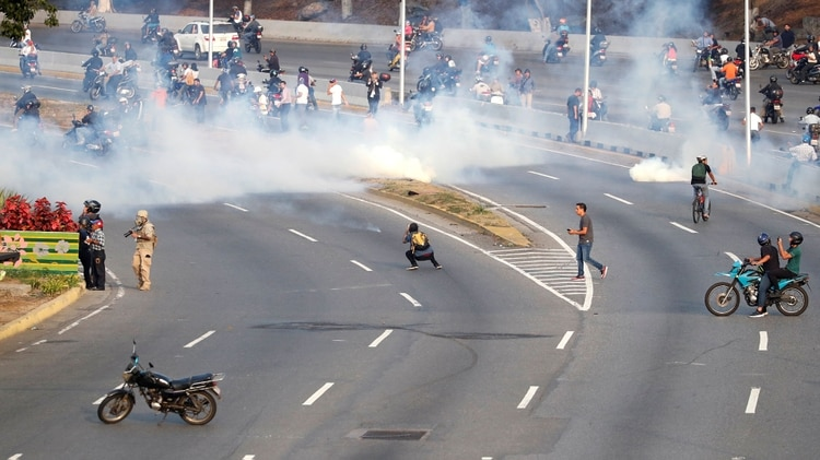 La gente huye de los gases lacrimógenos lanzados por las fuerzas chavistas. REUTERS/Carlos Garcia Rawlins