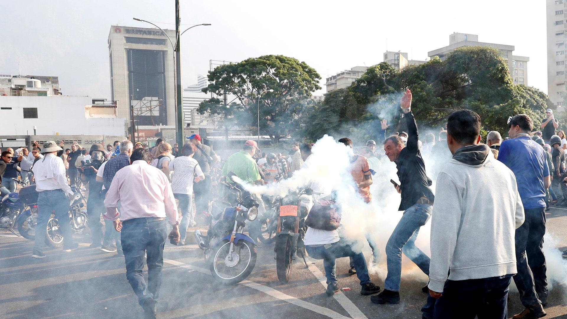 """La gente reacciona al gas lacrimógeno cerca de la Base Aérea Generalísimo Francisco de Miranda """"La Carlota"""", en Caracas, Venezuela, el 30 de abril de 2019."""